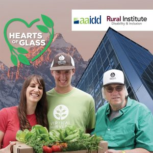 """Young woman, young man and middle-aged man smile and hold box of fresh lettuces and vegetables; modern-looking glass and steel building and mountains in the background; """"Hearts of Glass"""" film logo, a green outline of a heart adorned with leaves and text """"AAIDD and Rural Institute fofr Inclusive Communities"""" is at the top of the frame"""
